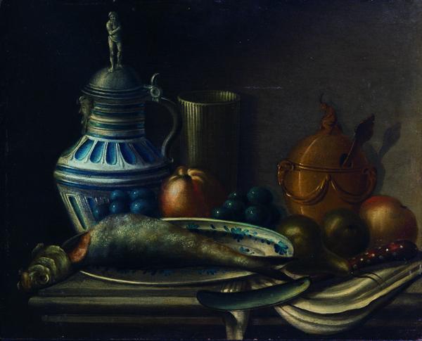 Aringa su un piatto di ceramica, frutta, due calici ed una brocca istoriata su un tavolo da cucina