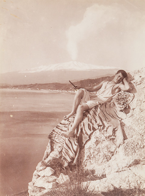 Young male posed on cliff with Etna in the background, ca. 1910