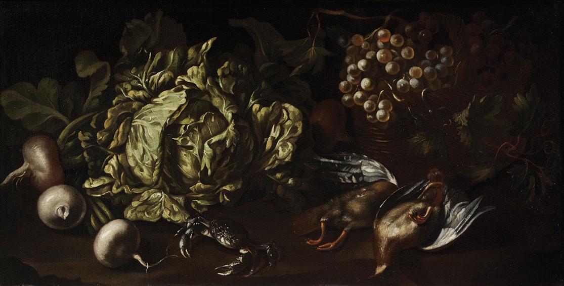 Una verza, rape, uva in un cesto di vimini, cacciagione di penna e un granchio su un piano