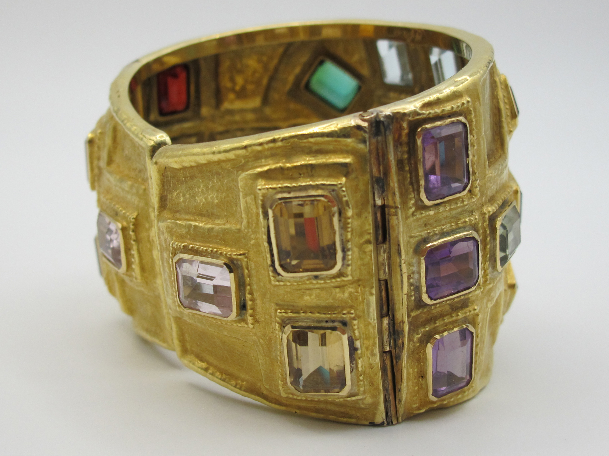 A gold and coloured gemstones bangle